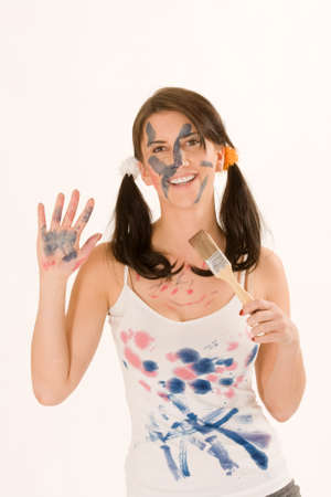 Young woman painting with paint on his face and hands photo