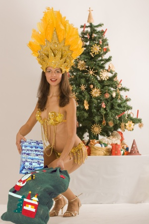 Beautiful samba girls from Santa Claus with sack before a Bavarian Christmas tree photo