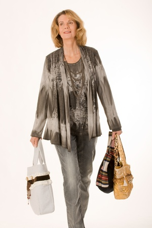 40 year old woman: older woman comes with a lot of shopping bags from. Stock Photo