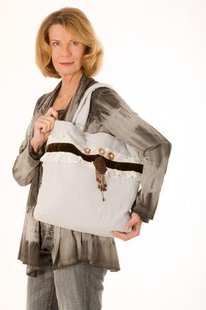 designer bag: older fashionably dressed woman with designer bag made of fabric
