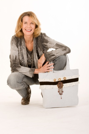 older woman with a fashionable bag is kneeling on the ground