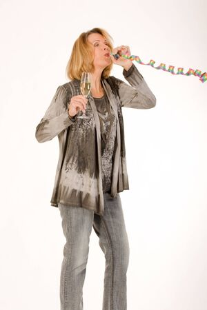 euphoria: older woman blows out a streamer and has a glass of champagne in hand Stock Photo