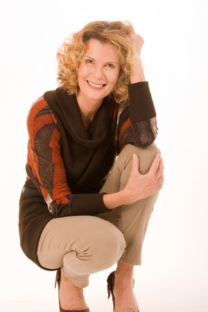 attractive older lady posing in front of the camera in a squatting position Standard-Bild