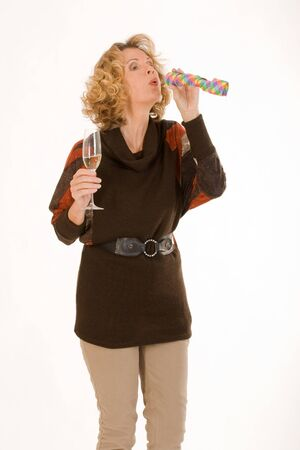 tipsy lady blows out a streamer and has champagne in hand photo