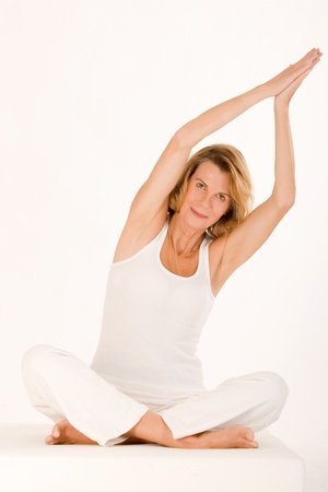 Older lady finds relaxation in yoga Stock Photo