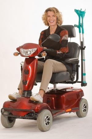 mujer mayor con discapacidad se mueve con muletas y auto eléctrico