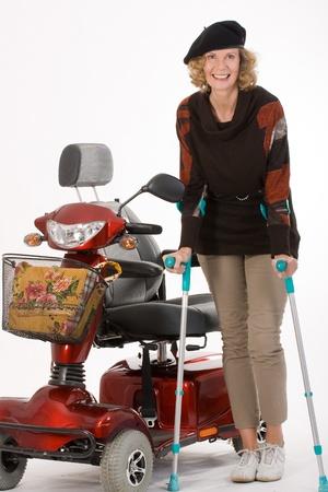 disability insurance: donna anziana con disabilit� si muove con le stampelle e auto elettriche Archivio Fotografico