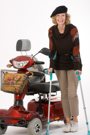 older woman with a disability moves on crutches and electric car