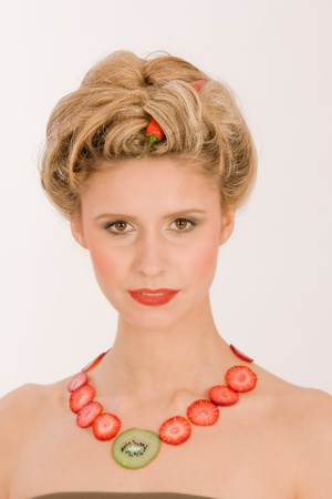 Attractive blonde young woman with strawberry-kiwi-chain photo