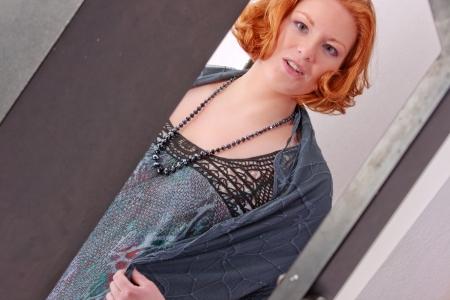 traje de gala: Elegante mujer de pelo rojo en vestido de noche con un ligero predominio Foto de archivo