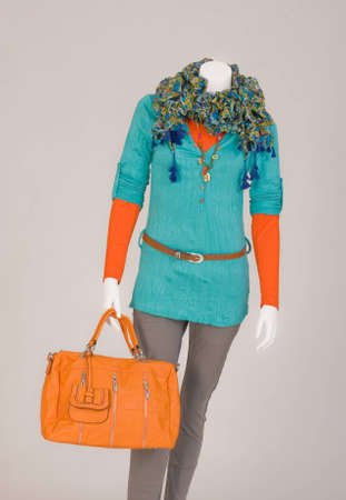 Mannequin dressed with a scarf, T-shirt, beige pants and orange bag photo