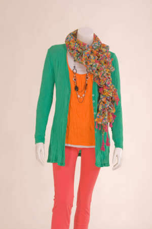 Mannequin dressed with a scarf, jacket, shirt and green pants photo