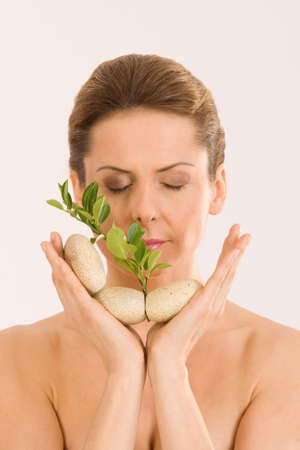 The woman relaxing with closed eyes, with pebbles and a herb in your hand Stock Photo - 12943284