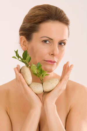 young woman with an aromatherapy with herbs and stones photo