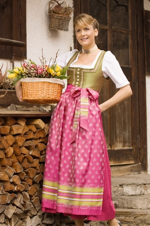 Bavarian girl sitting on a bench in dress and bouquet of Easter basket photo
