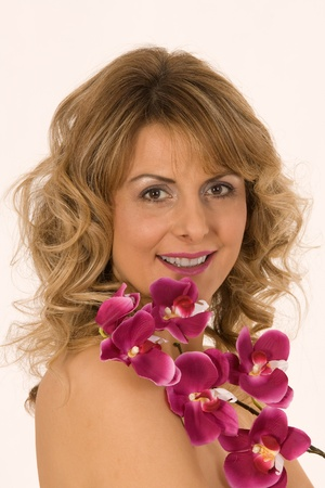Portrait of a smiling woman with orchid on the chest Stock Photo - 12943350