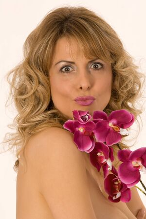 Portrait of woman with orchid on the chest and kissing lips photo