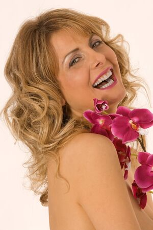 Portrait of a smiling woman with orchid on the chest  photo