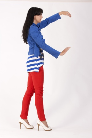 Model posing with red pants, striped shirt and blue jacket photo