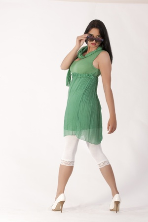 nude little girls: Young woman in a green tunic with leggings and sunglasses