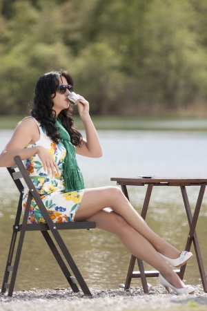 Fashionable business woman at a coffee break at the lake photo