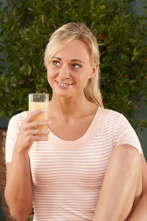 Young woman drinking a glass of healthy juice photo
