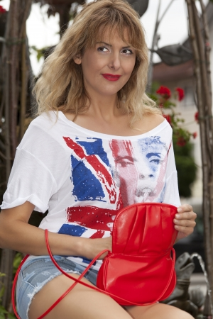 Fashionable women in party outfit is looking for something in your bag photo