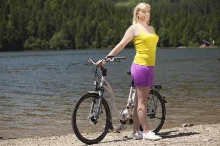 Young woman with bicycle on a lakeshore photo