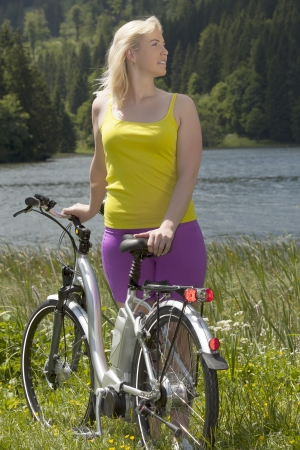 Young woman on vacation with bicycle Stock Photo