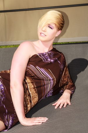 Young blonde Plus Size Model enjoys the sun s rays are in a fashionable dress photo