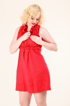Blonde woman in a red dress with romantic expression photo