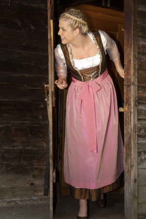 Dairymaid in a dirndl looks out the door on the farm
