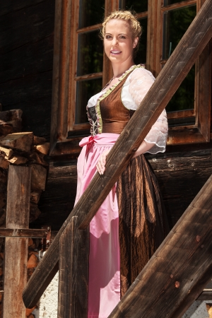 Bavarian girl is in festive costume on a mountain, stairs photo