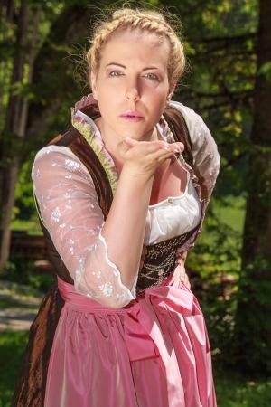 Bavarian girl in festive costumes handing out kisses photo