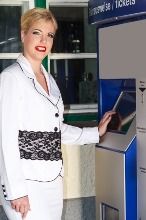 Elegant business woman wants to buy a ticket at the vending machine photo