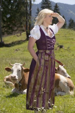 Giovane donna in un dirndl in un prato alpino con mucche godersi la vista photo