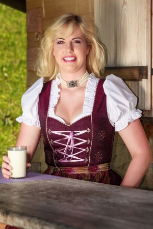 Young Peasant Woman in dirndl with a glass of milk photo