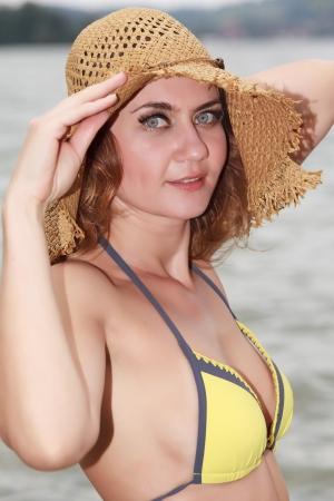 Portrait of a radiant woman with straw hat in bikini Stock Photo - 15229429