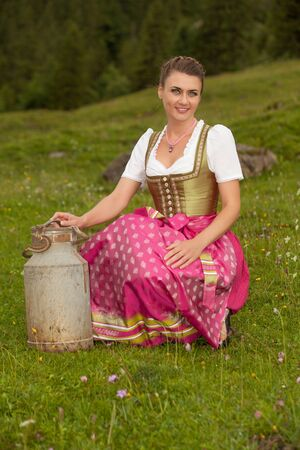 Young woman in traditional dress with milk jug sitting in the meadow Stock Photo - 15155538