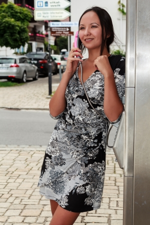 fair skinned: Young woman on the phone a pay phone