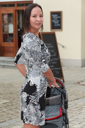 Young woman in stylish outfit goes walking with stroller photo
