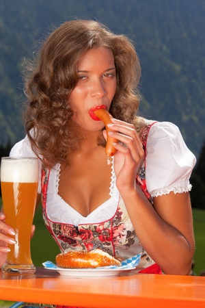 dirndl: Young Brazilian food in Bavarian costume with sausages