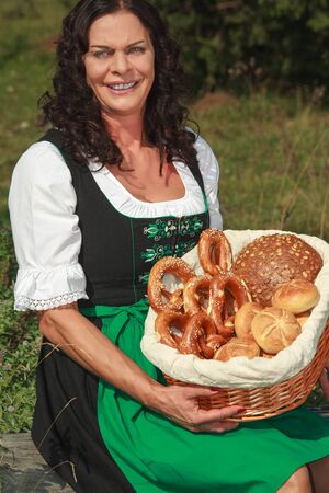 Senior Woman on the meadow with a basket of baked goods Stock Photo - 15389008