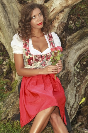 dark skinned: Brazilian woman in Bavarian dress with roses in hand dreams to himself