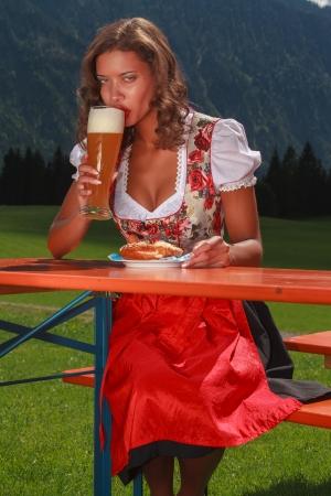 Bavarian girl in costume enjoys a wheat beer