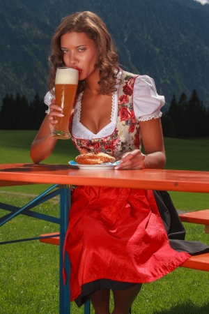 Bavarian girl in costume enjoys a wheat beer  photo