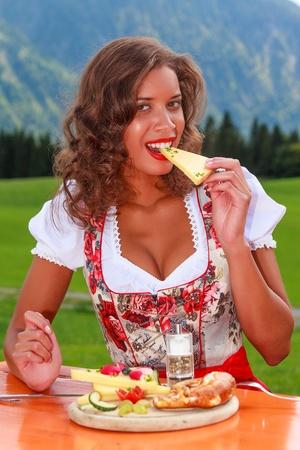 Bavarian girl in eating cheese  Standard-Bild