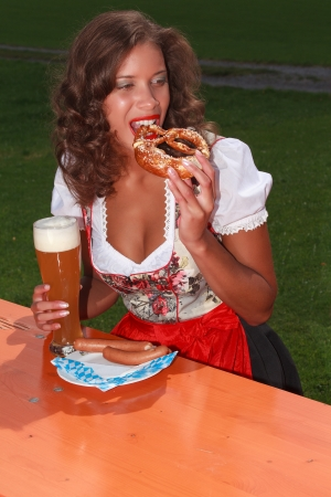 Young girl eating in Bavarian costume at and drink Stock Photo - 16409617