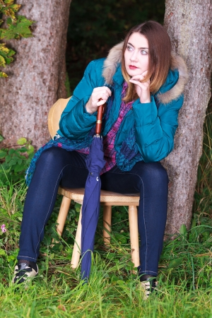 femal: Young woman with umbrella in very fashionable clothes sitting in the forest