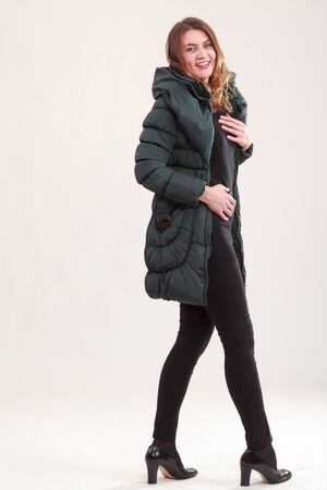 Young woman with green down coat and elegant sweater with black pants Stock Photo - 16409747